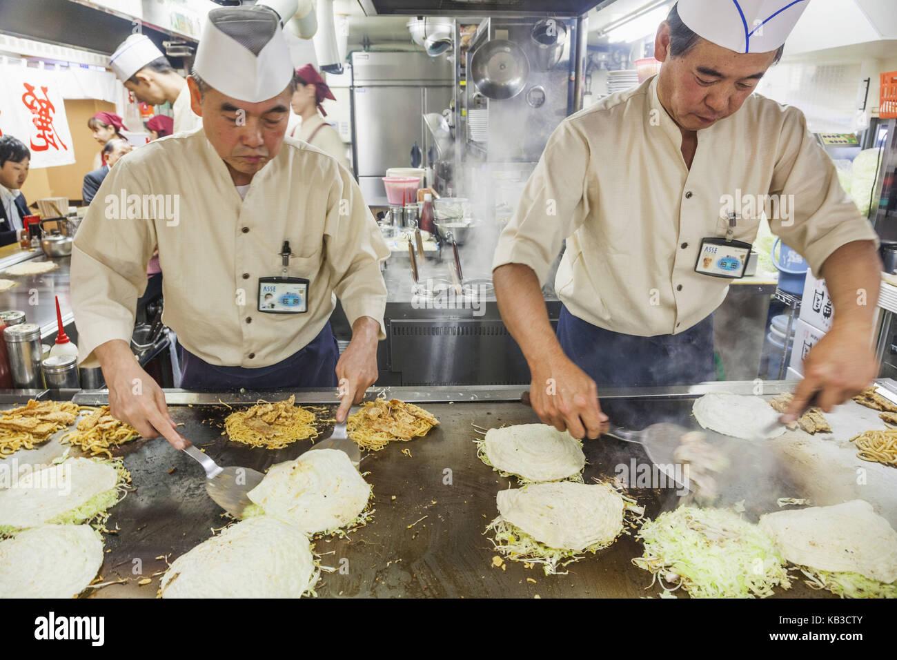 Japan, Kyushu, Hiroshima, restaurant, cooks while preparation of Okonomiyaki, Stock Photo