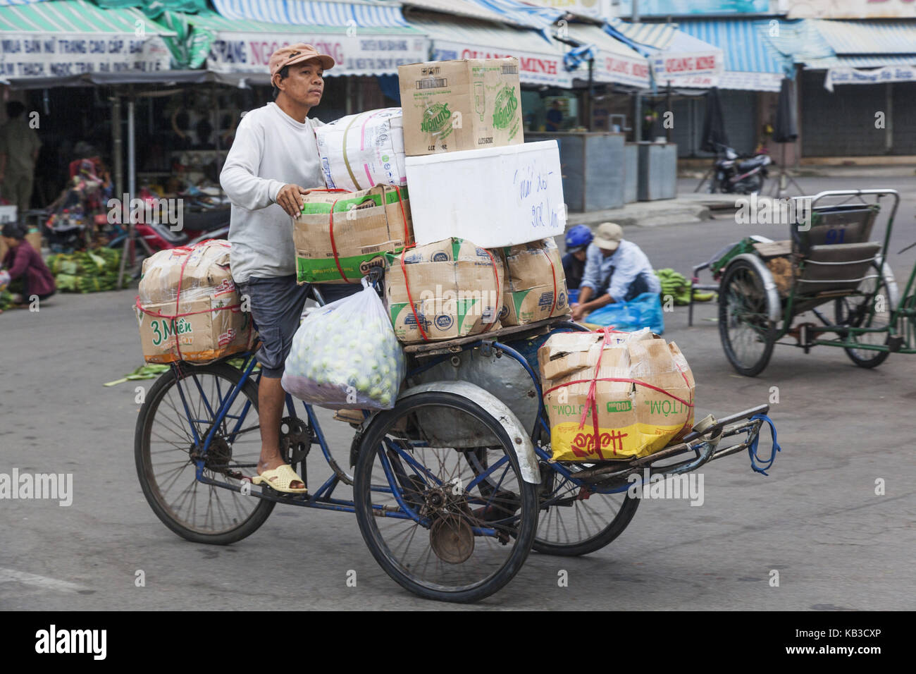 Vietnam, Nha Trang, central market Cho Dam, man carries goods on fully charged tricycle, - Stock Image