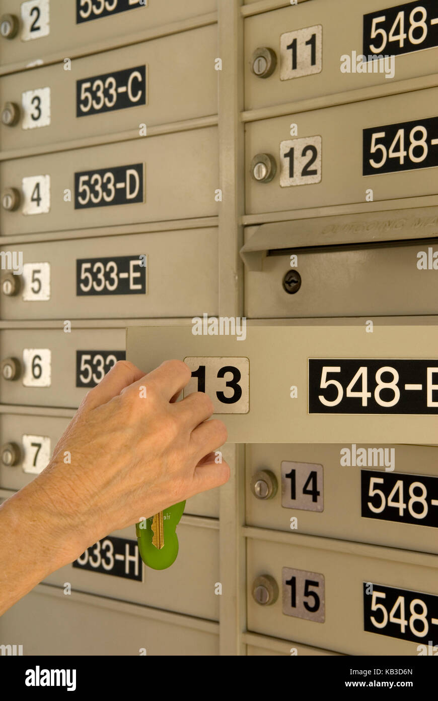Caucasian woman opening apartment complex mailbox with key ...