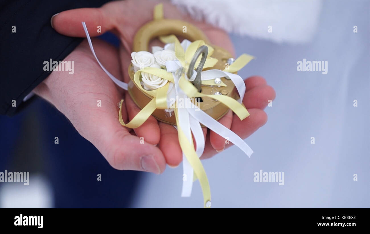 Wedding symbol, lock in hands of bride and groom. Newlyweds fix the lock on the bridge as a symbol of love. Padlock - Stock Image