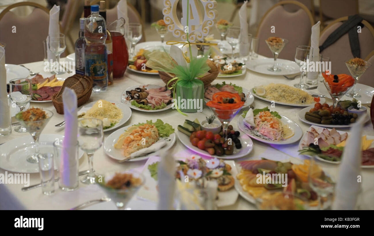 Table with food and drink. Catering table set service with silverware and glass stemware at restaurant before party. - Stock Image