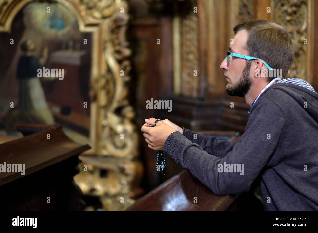 Young man with glasses and beard praying in a church - Stock Image