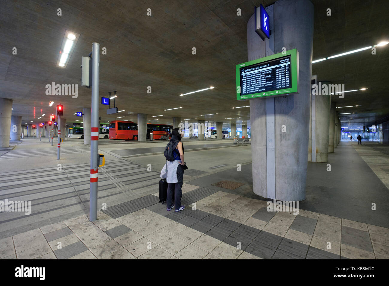 Passenger looking at schedule board while waiting for a bus at Vienna Central Station, Vienna, Austria, Europe - Stock Image