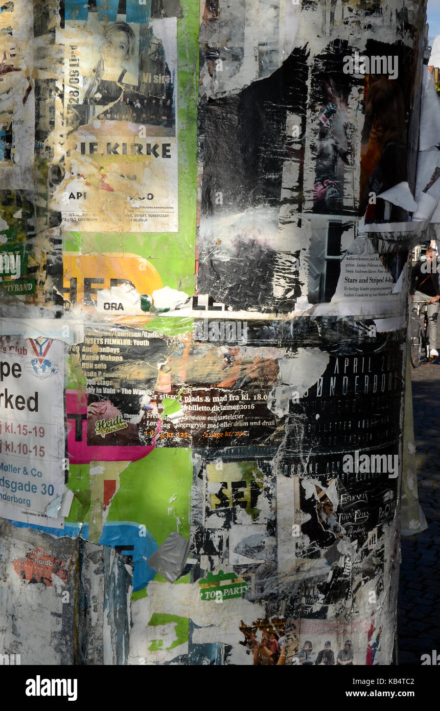 Poster wall with remain of posters from different arrangements. - Stock Image