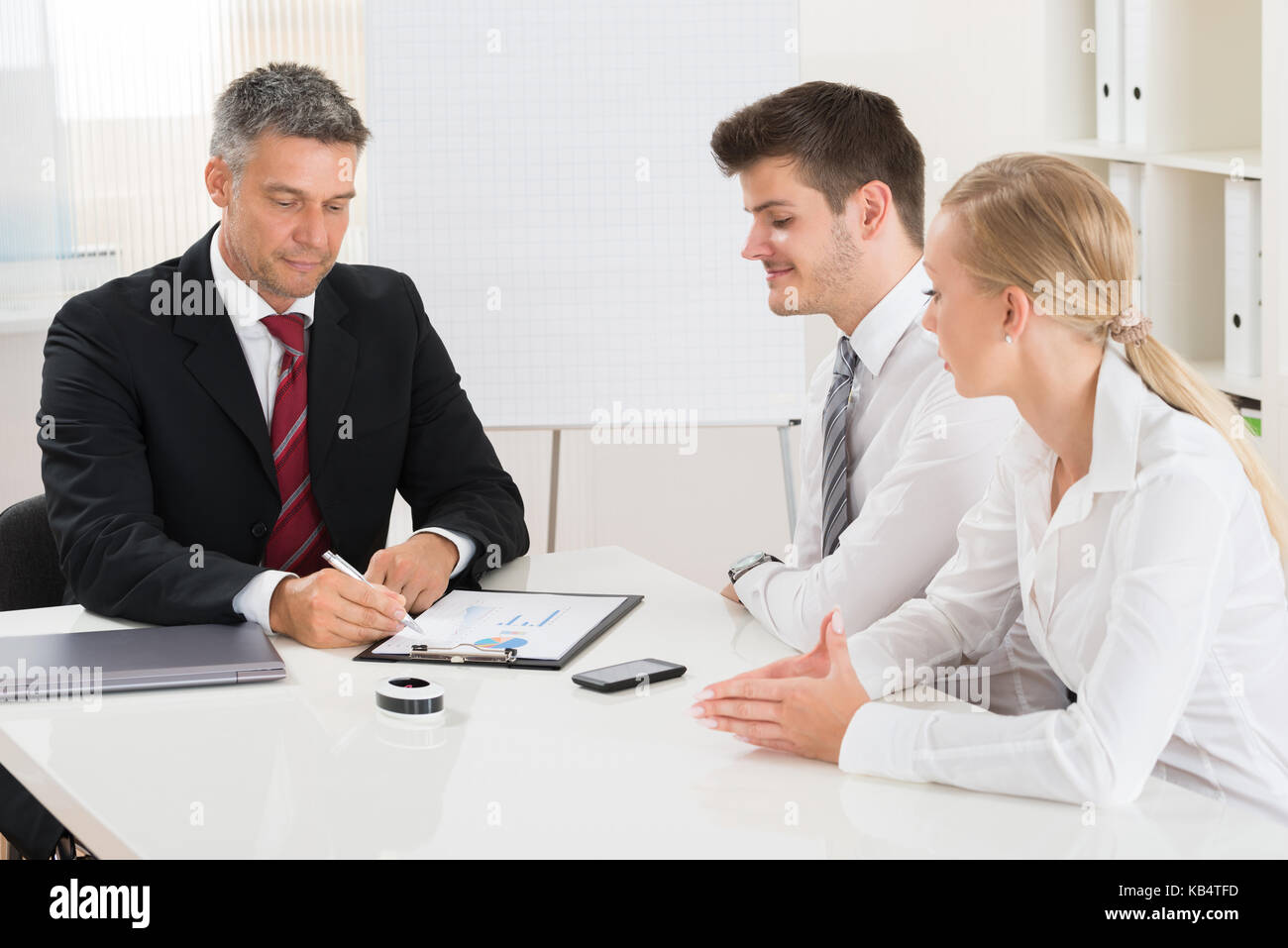 Group Of Businesspeople Discussing On Graph At Desk Stock Photo