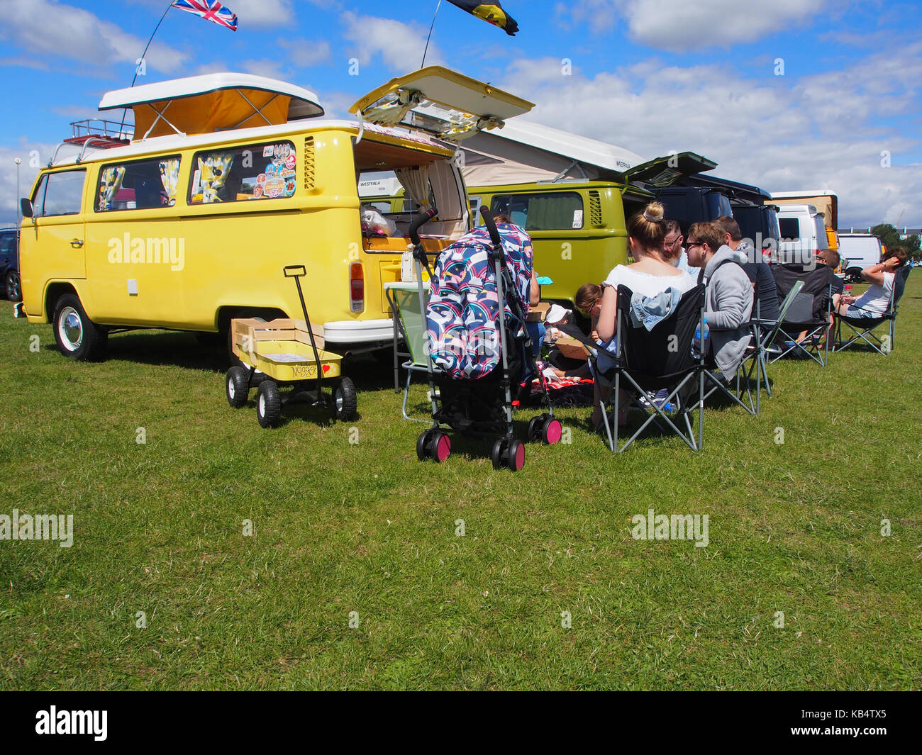 people on camping chairs enjoying a VW campervan meet - Stock Image