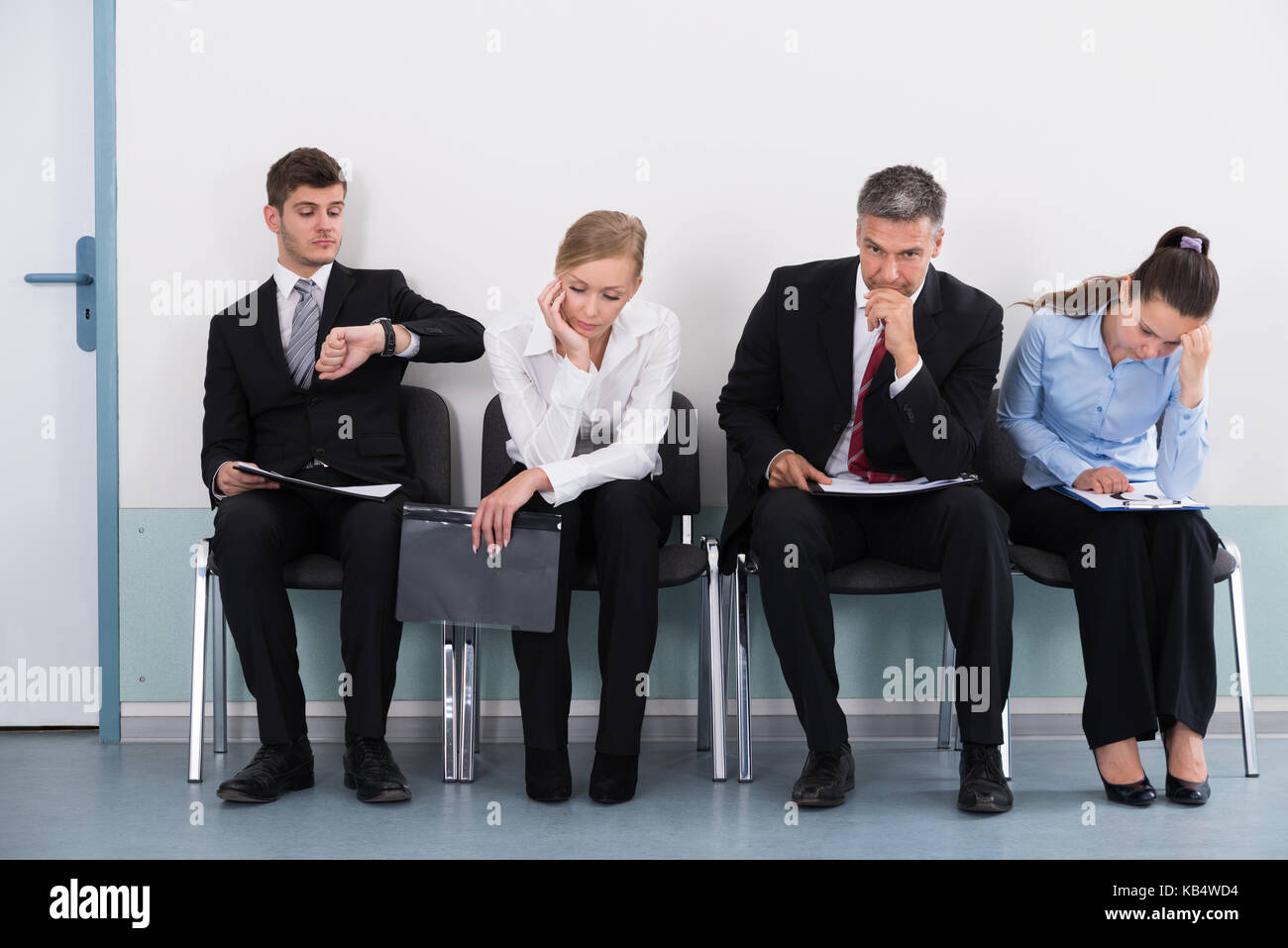 Businesspeople Sitting On Chair Waiting For Job Interview In Office - Stock Image