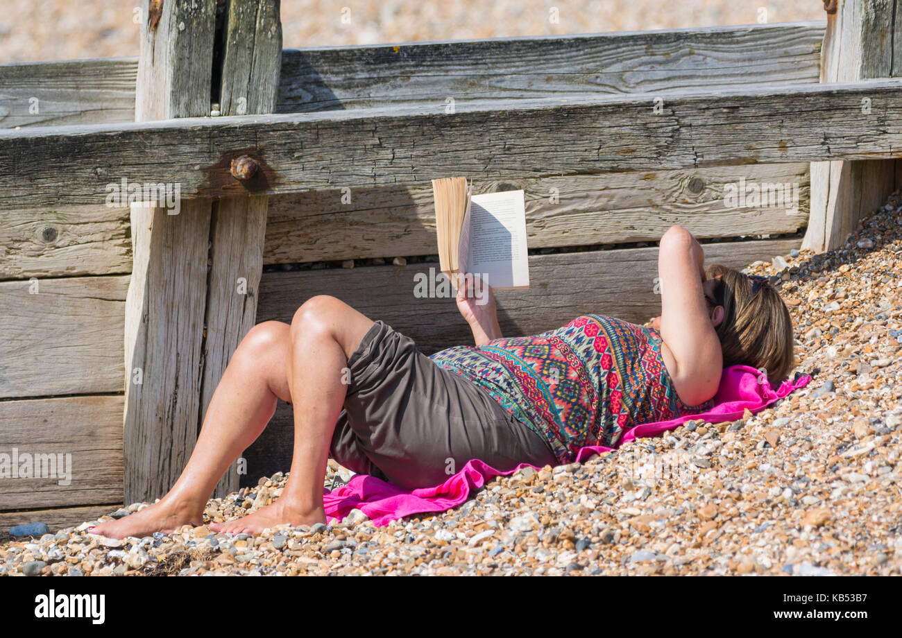 Woman laying on a beach reading a book. - Stock Image