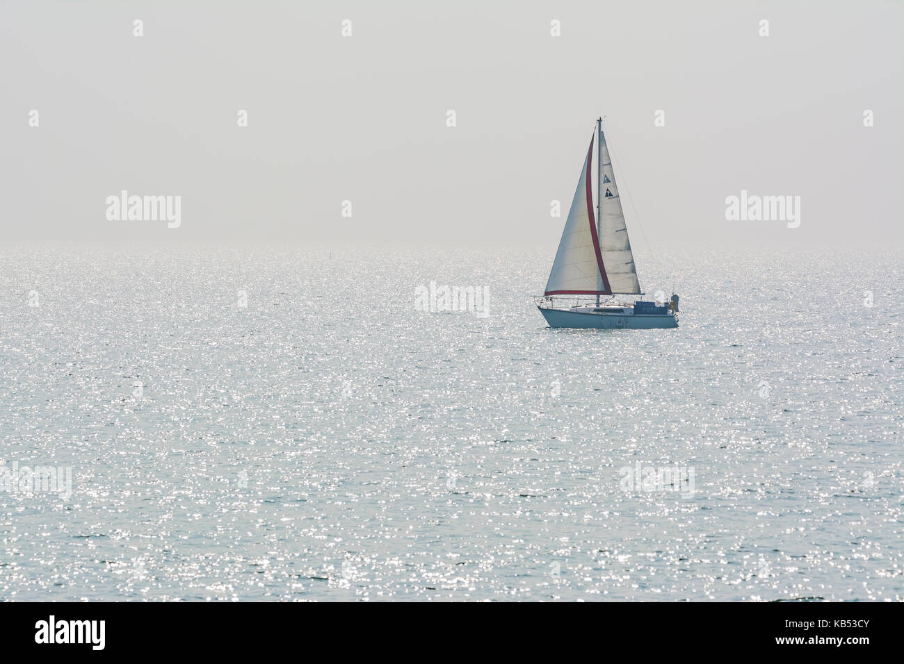 Small yacht on the sea with sun sparkling in the water. Small sailing boat on the ocean with reflecting sun sparkles. - Stock Image