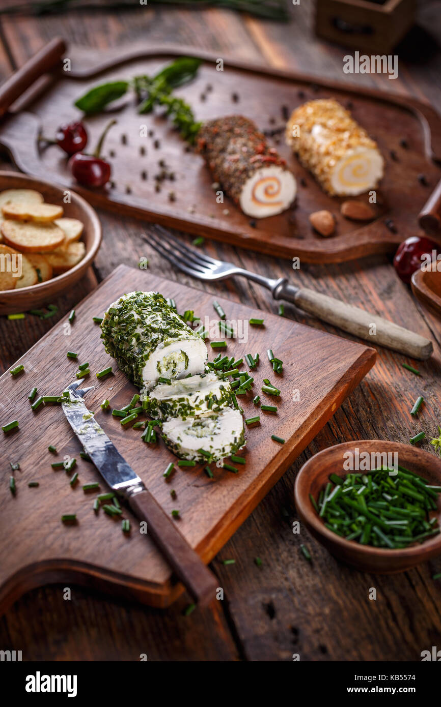 Cheese appetizer. Delicious soft cheese with fresh herbs served on a cutting board - Stock Image
