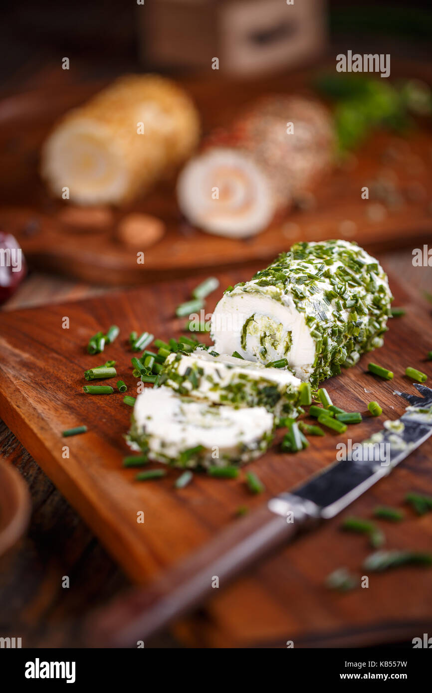 Delicious soft cheese with fresh herbs served on a cutting board - Stock Image