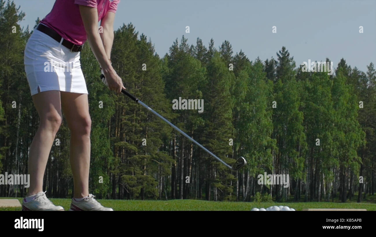 Golf player attempting the first stroke in the teeing area. Only legs of player to be seen - Stock Image