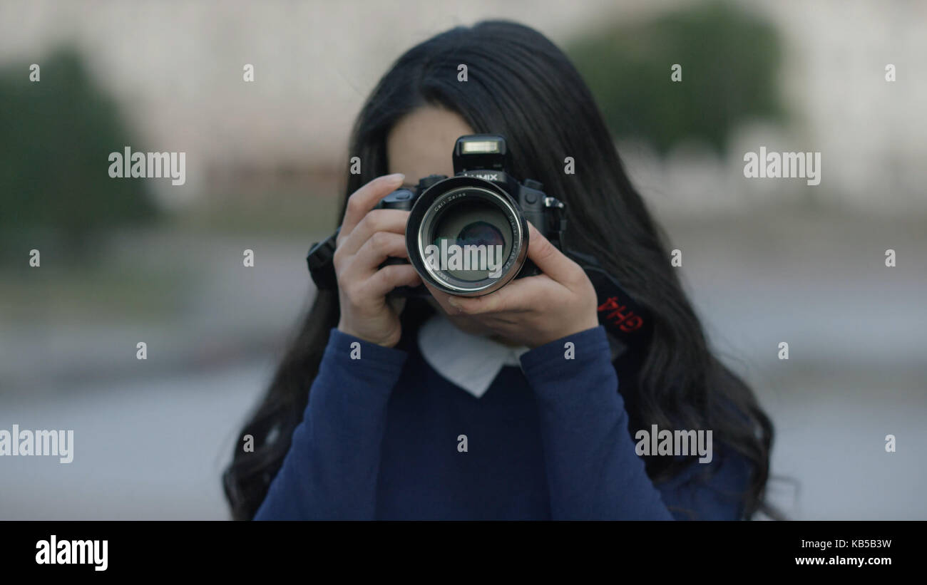 Photographer covering her face with the camera. Woman with photocamera - Stock Image