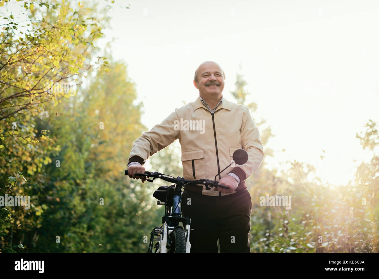 Senior man go for a walk with bike in countryside - Stock Image