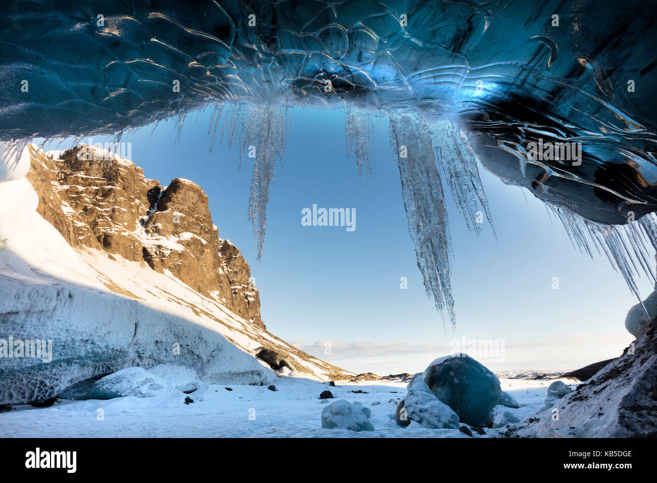 View from ice cave towards sunlit mountains with icicles hanging from cave entrance, near Jokulsarlon, South Icelan - Stock Image