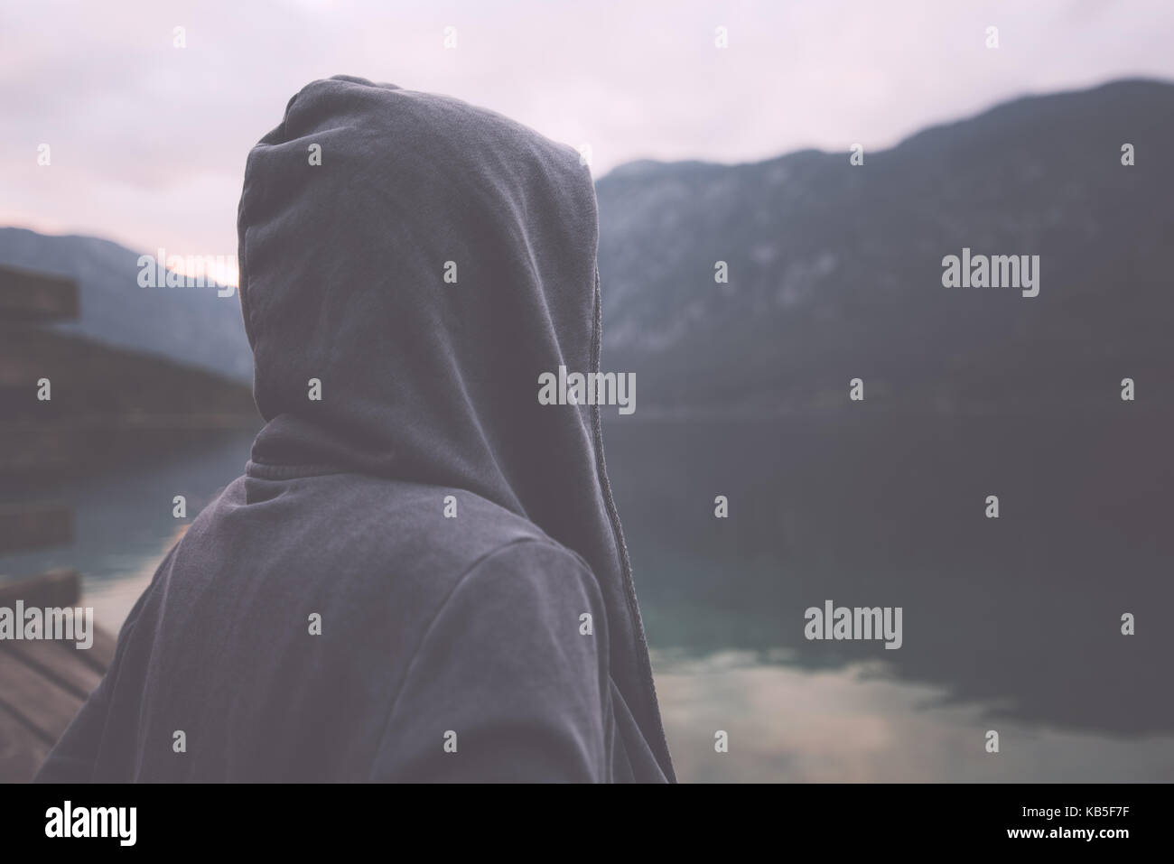 Gloomy nostalgic portrait of sad lonely melancholic adult female with hooded jacket standing on the lake shore in - Stock Image