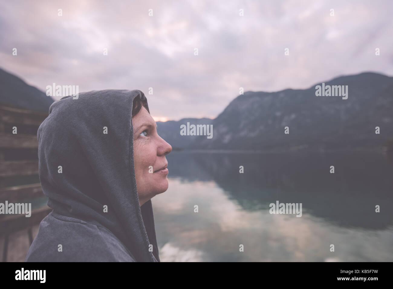 Nostalgic portrait of lonely melancholic adult female with hopeful look towards the sky standing on the lake shore - Stock Image