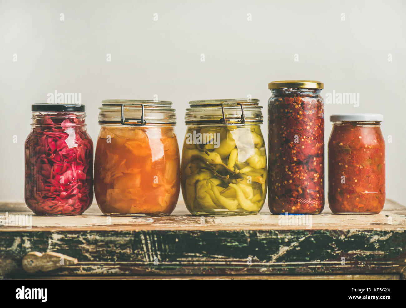 Autumn pickled colorful vegetables in jars placed in row - Stock Image