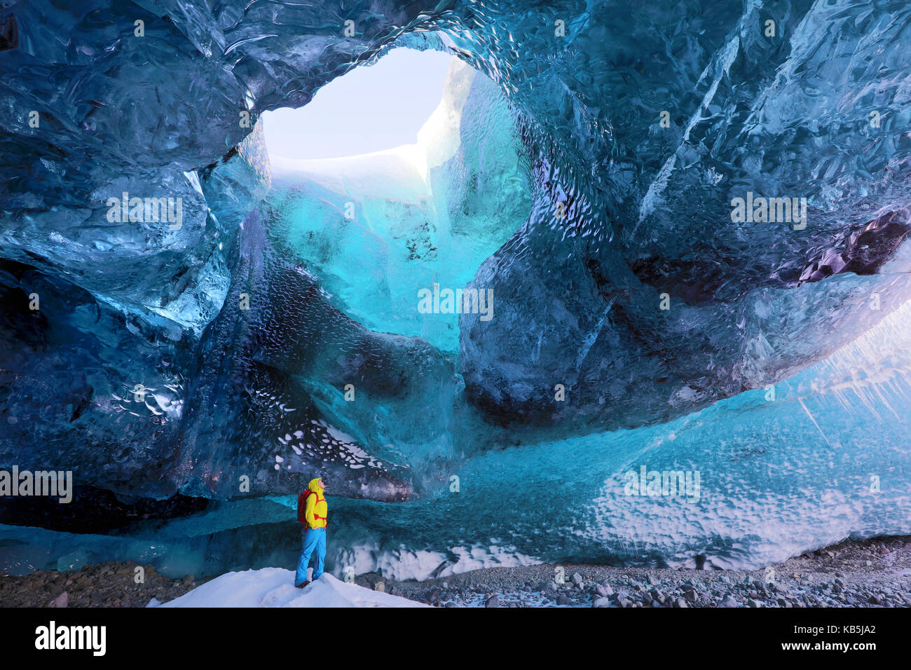 Inside ice cave under the Vatnajokull Glacier, with cave guide looking up to hole in cave roof, near Jokulsarlon, - Stock Image
