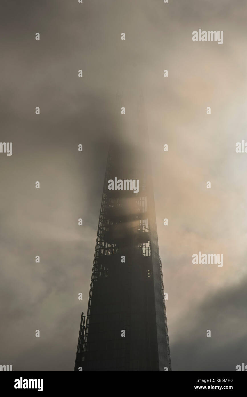 London, UK. 28th Sep, 2017. UK Weather. Storm clouds blot out the sun and sometimes obscure the top of the Shard. - Stock Image