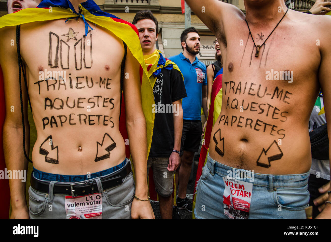 Barcelona, Spain. 28th Sep, 2017. Two students without shirt display text painted on their skin 'get out me - Stock Image
