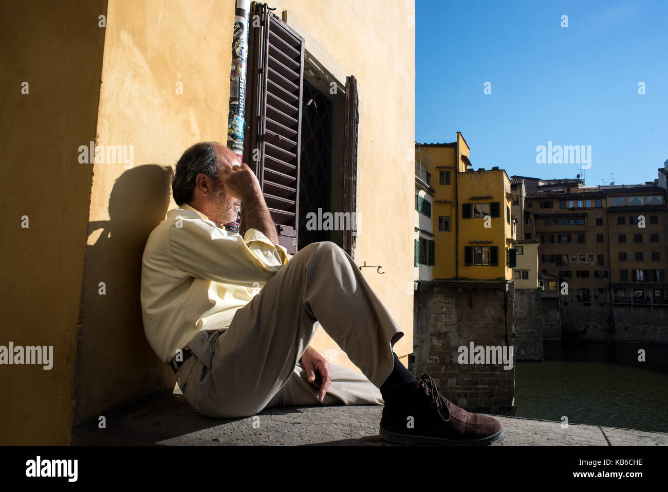 A man sits thoughtfully on the Arno river bank with Ponte Vecchio bridge on the back. Florence, Italy - Stock Image
