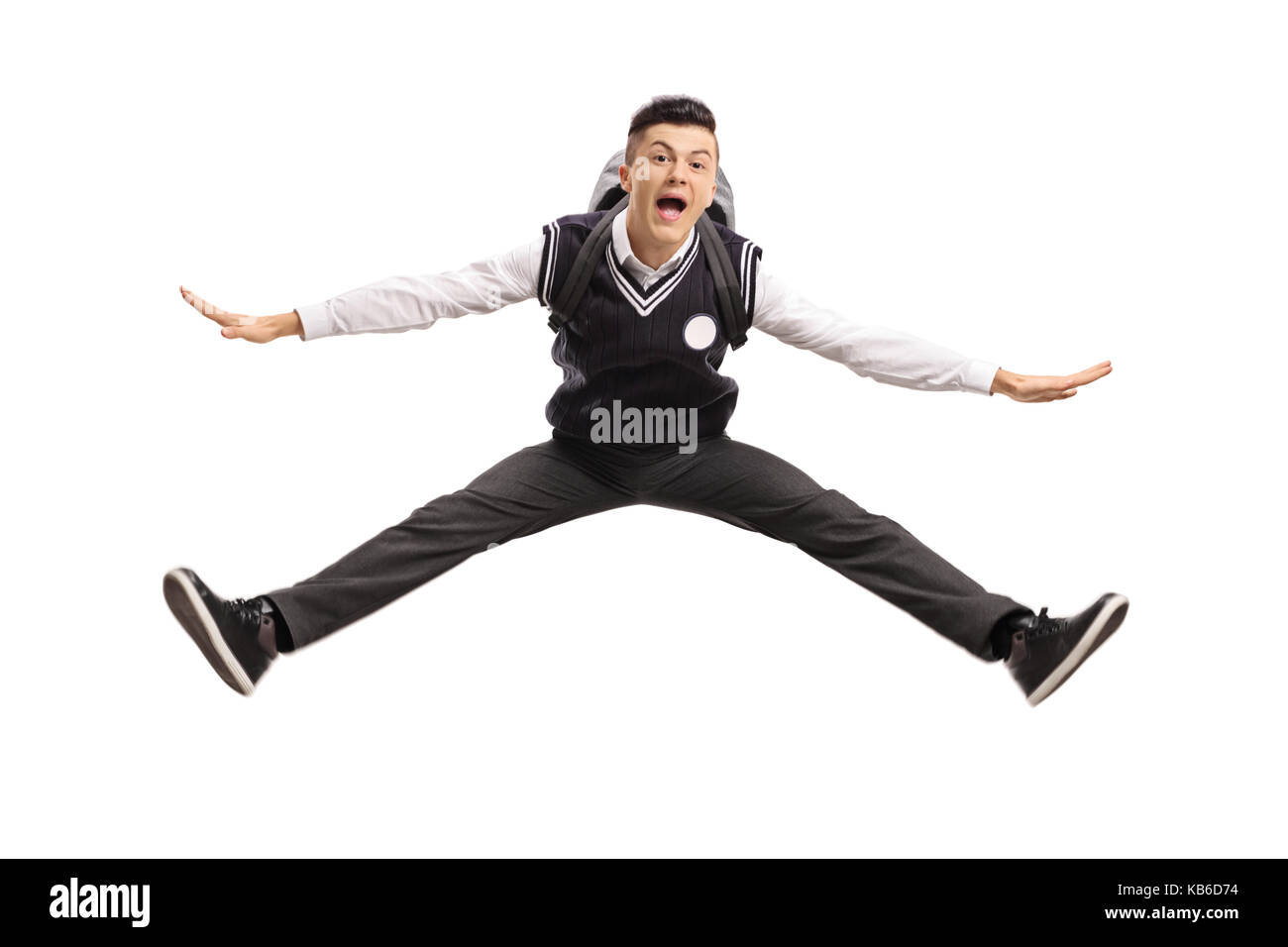 Overjoyed teenage student in a uniform jumping isolated on white background - Stock Image