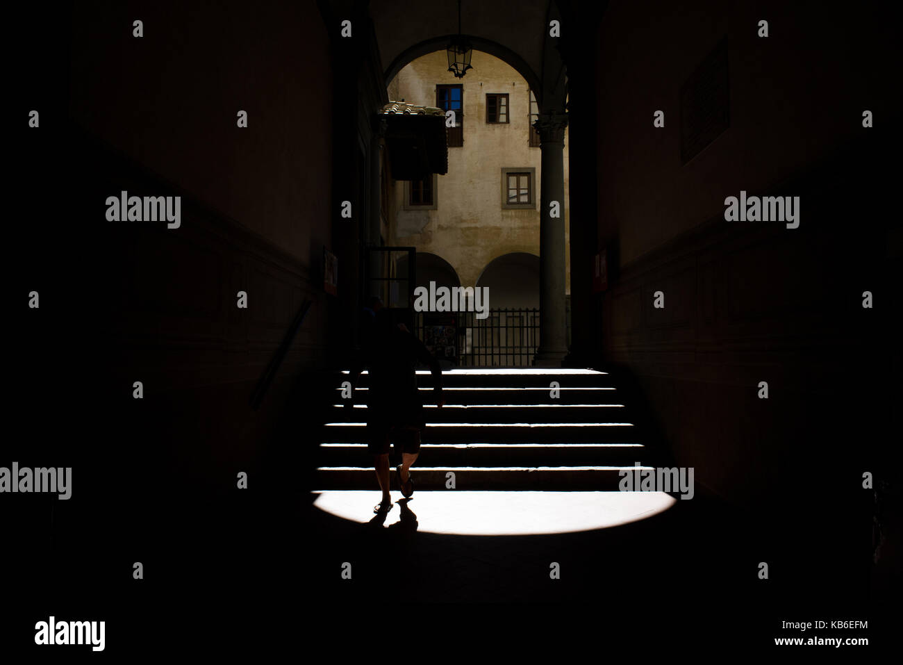A man goes down the stairs backlit in the Badia Fiorentina in Florence, Italy Stock Photo