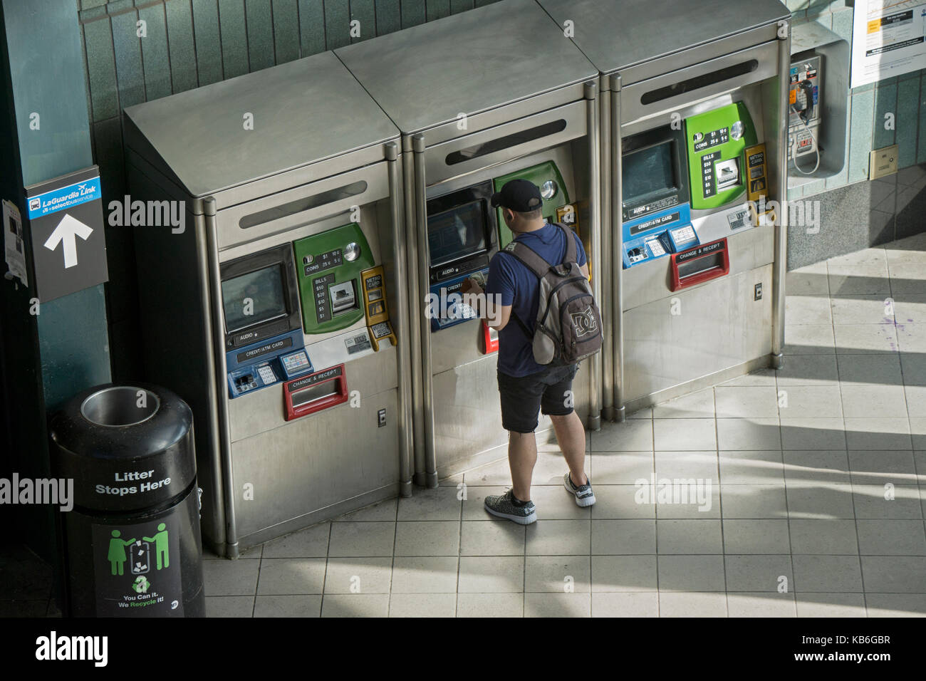 A young man with a backpack purchasing or refilling his Metrocard at the 74th Street Broadway station on the 7 line. - Stock Image