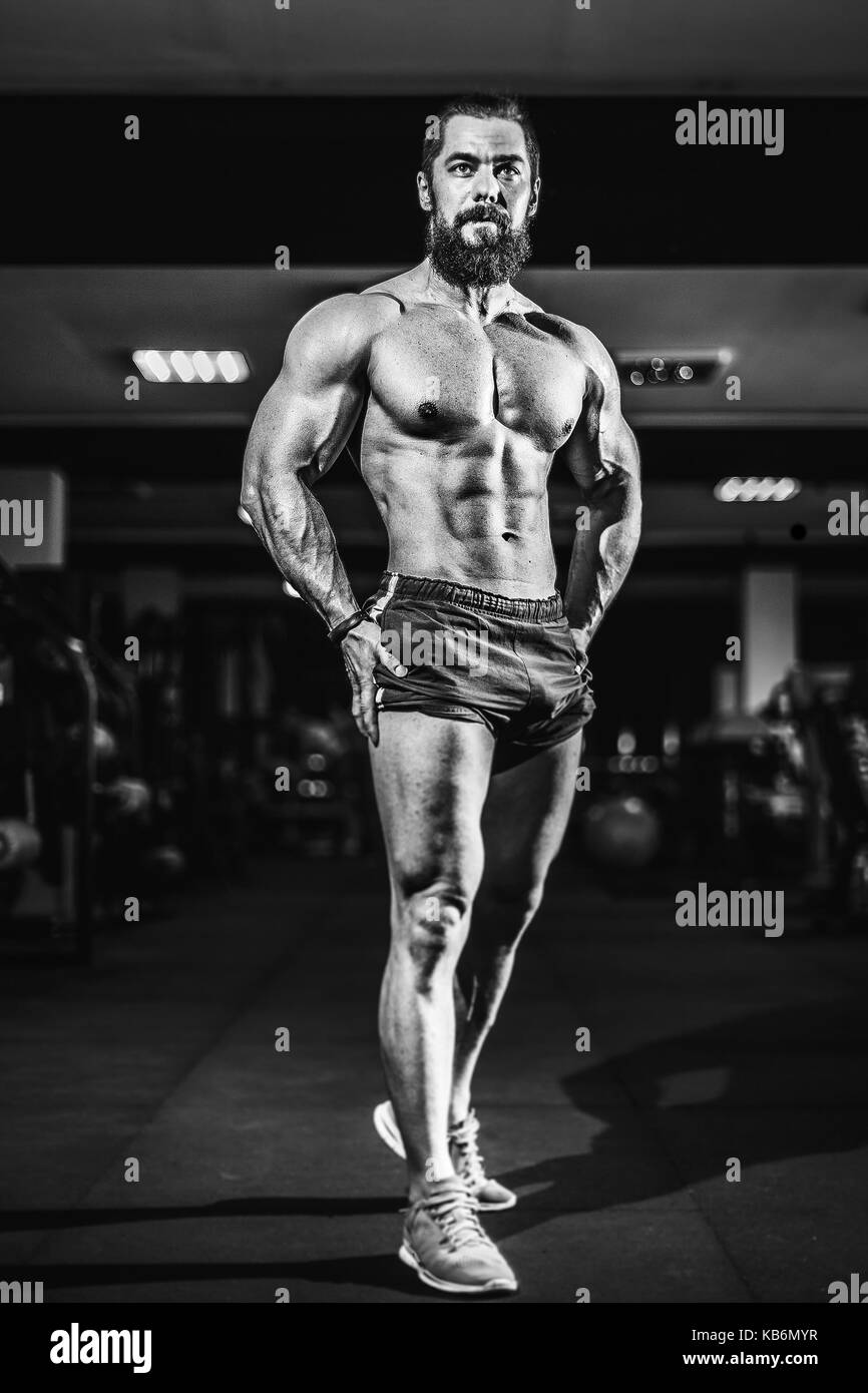 Athlete muscular bodybuilder man posing in gym. - Stock Image