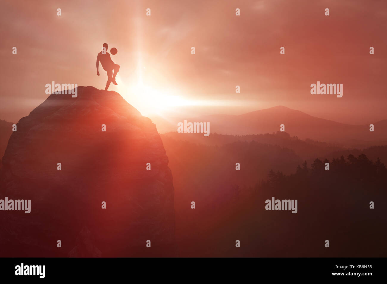 Silhouette of a soccer player  against trees and mountain range against cloudscape - Stock Image