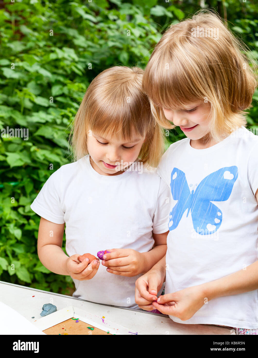 Two little girls are playing with  modelling clay outdoor - Stock Image