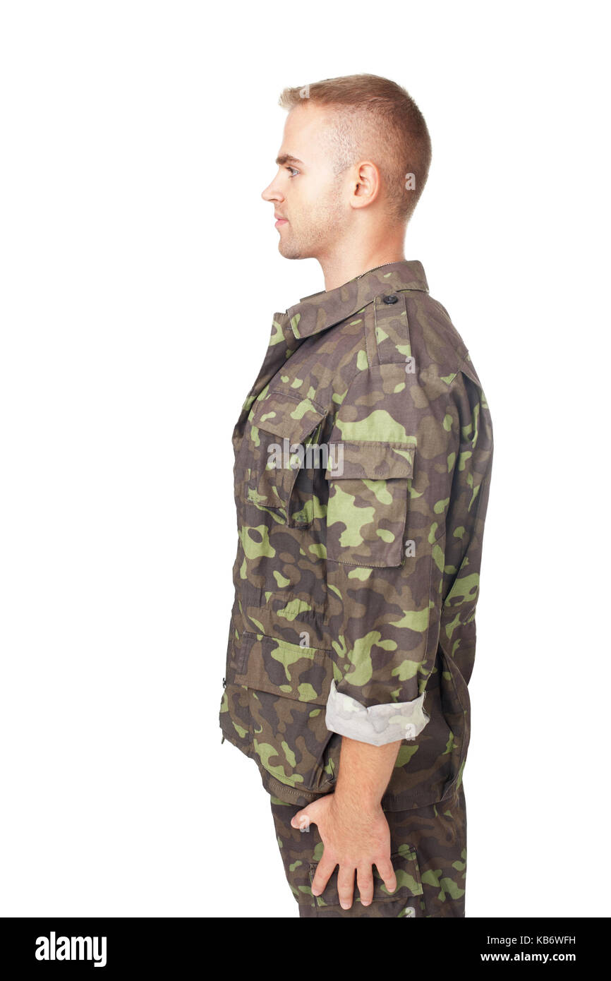 side view of young army soldier standing in attention isolated on white background. - Stock Image