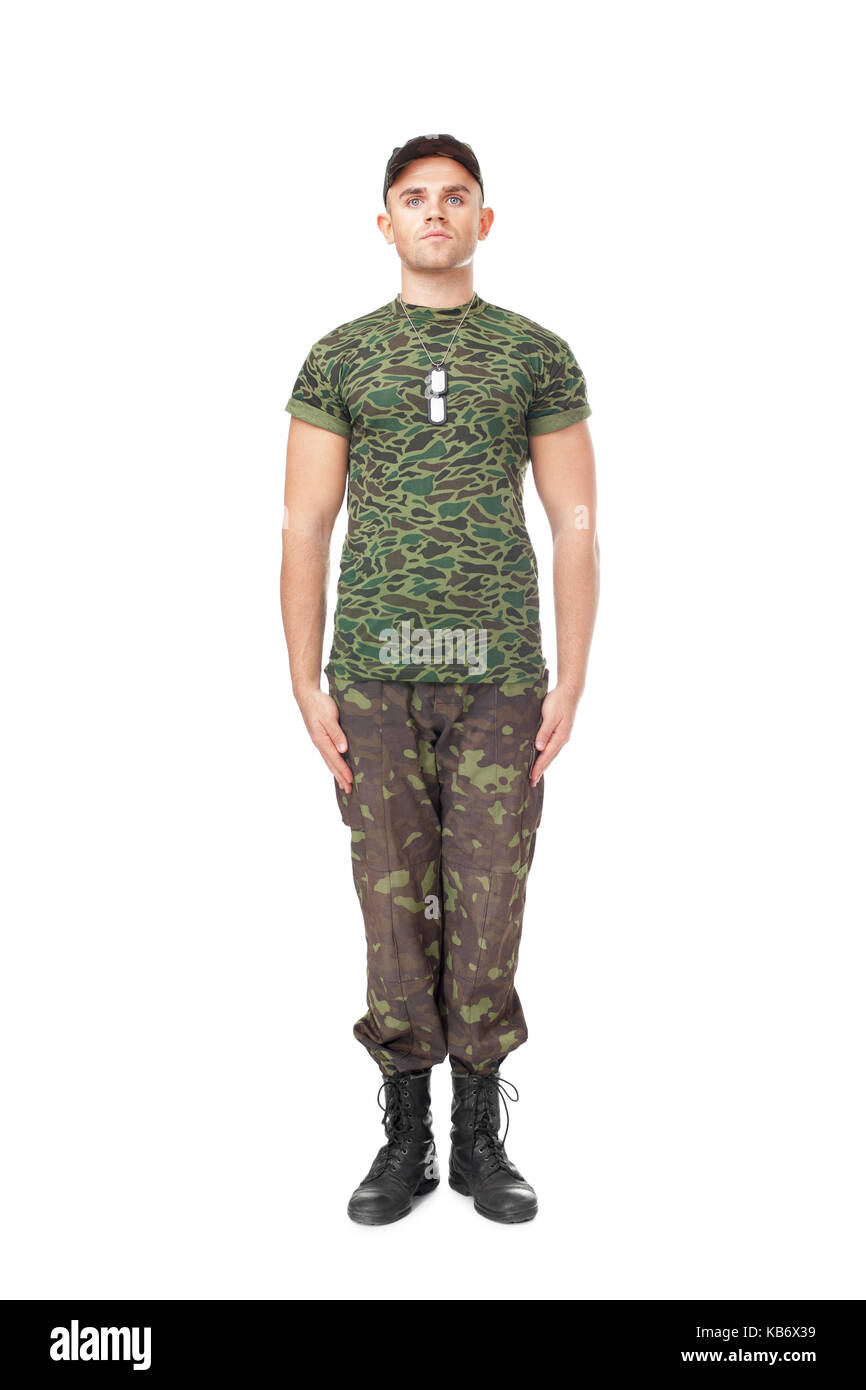 Full length portrait of young army soldier standing in attention isolated on white background - Stock Image