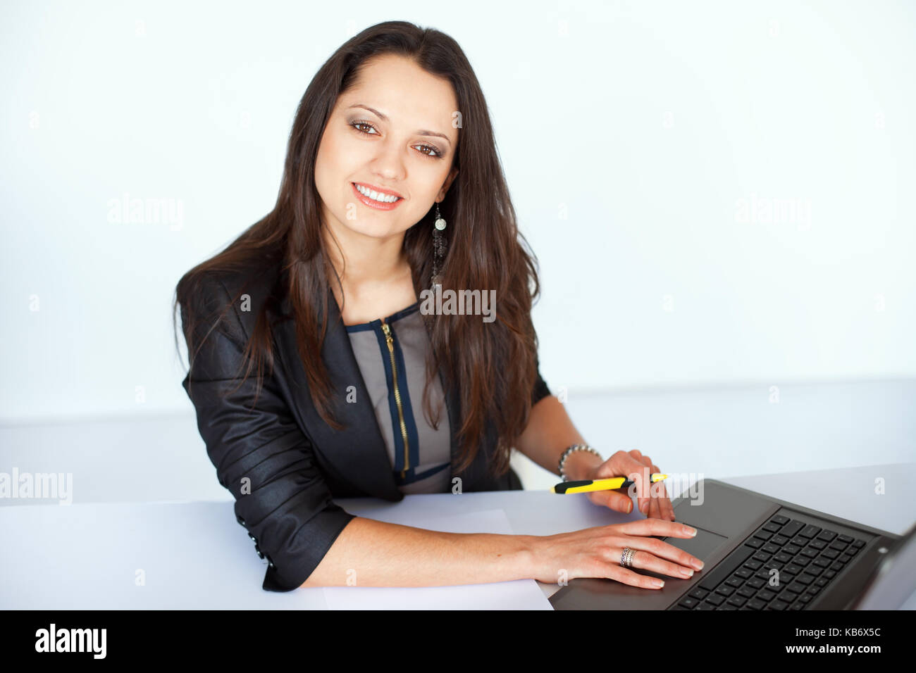 Portrait of beautiful young smiling brunette business woman working on a laptop in office - Stock Image