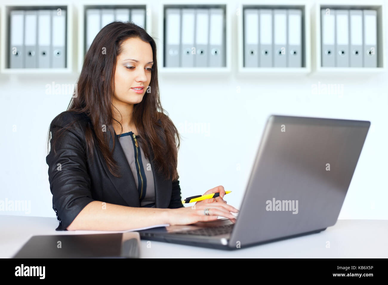 Portrait of beautiful young brunette business woman working on a laptop in office - Stock Image