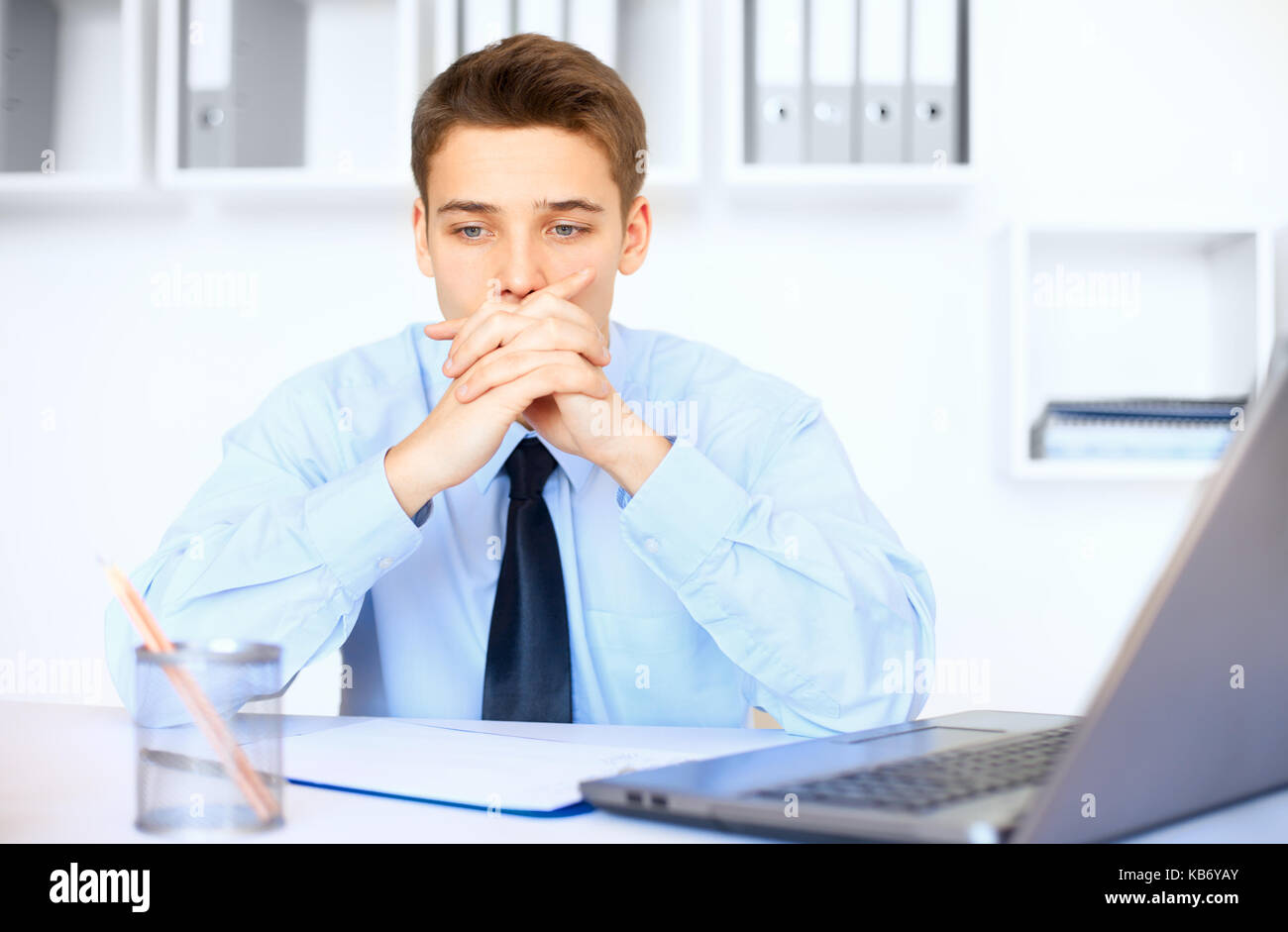 Portrait of young pensive businessman at his workplace in bright office - Stock Image