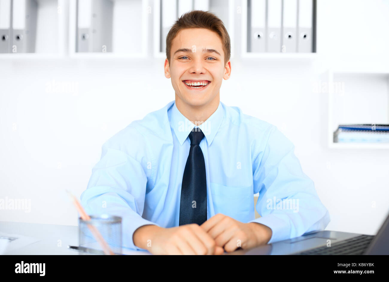 Portrait of young laughing businessman at his workplace in bright office - Stock Image