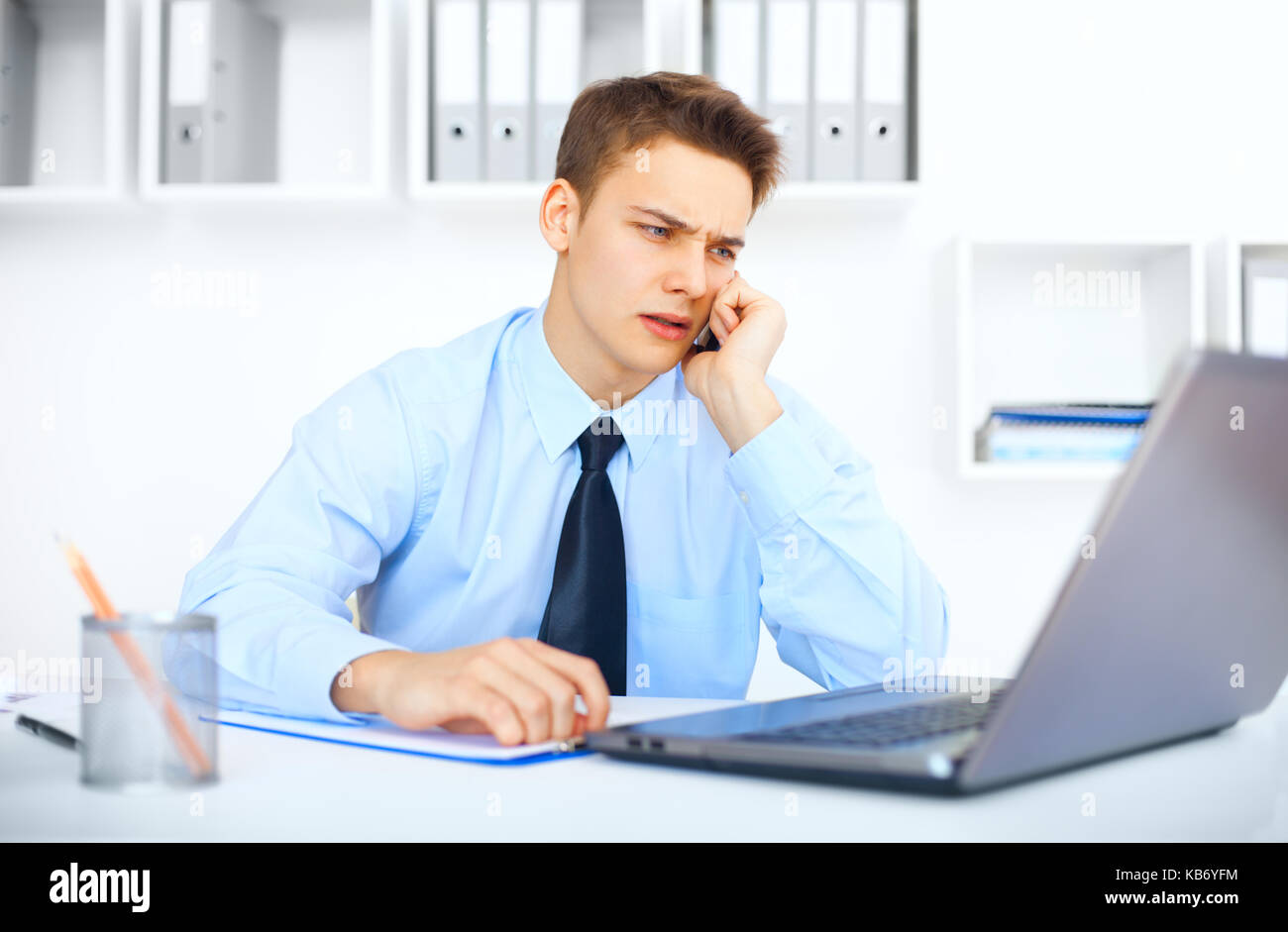 Portrait of young pensive businessman talking on cell phone in office Stock Photo