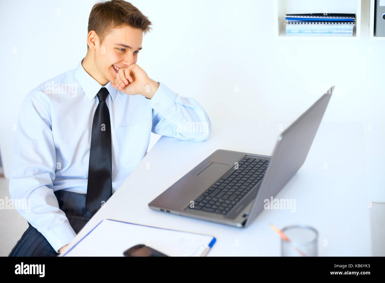Portrait of young laughing businessman looking at the laptop screen at his workplace in bright office - Stock Image
