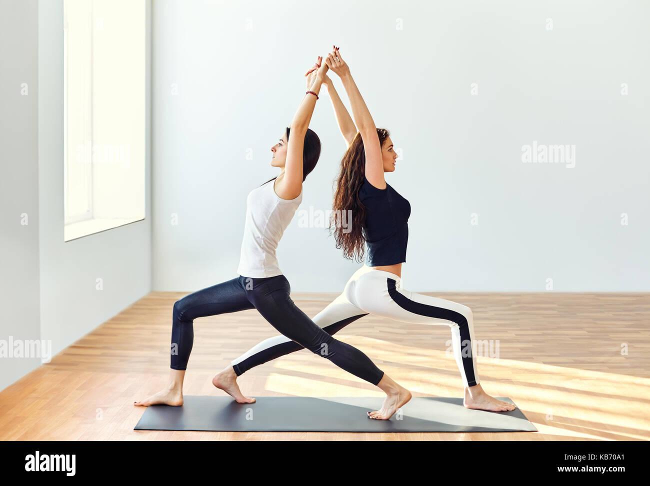 Two young women doing yoga asana warrior one pose. Virabhadrasana