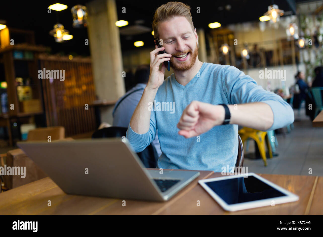 Young man having phone call in coffee shop - Stock Image