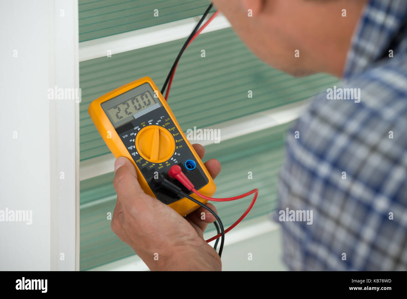 Cropped image of male repairman checking fridge with digital multimeter at home - Stock Image