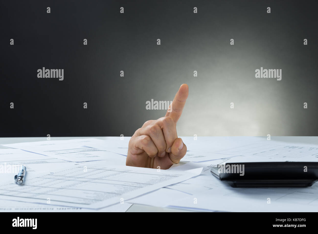 Closeup of businessman's hand emerging from documents - Stock Image
