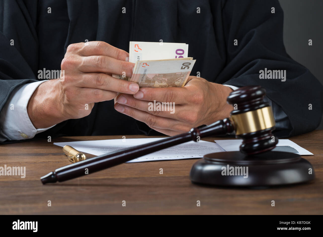 Male corrupt judge counting money at table in courtroom Stock Photo