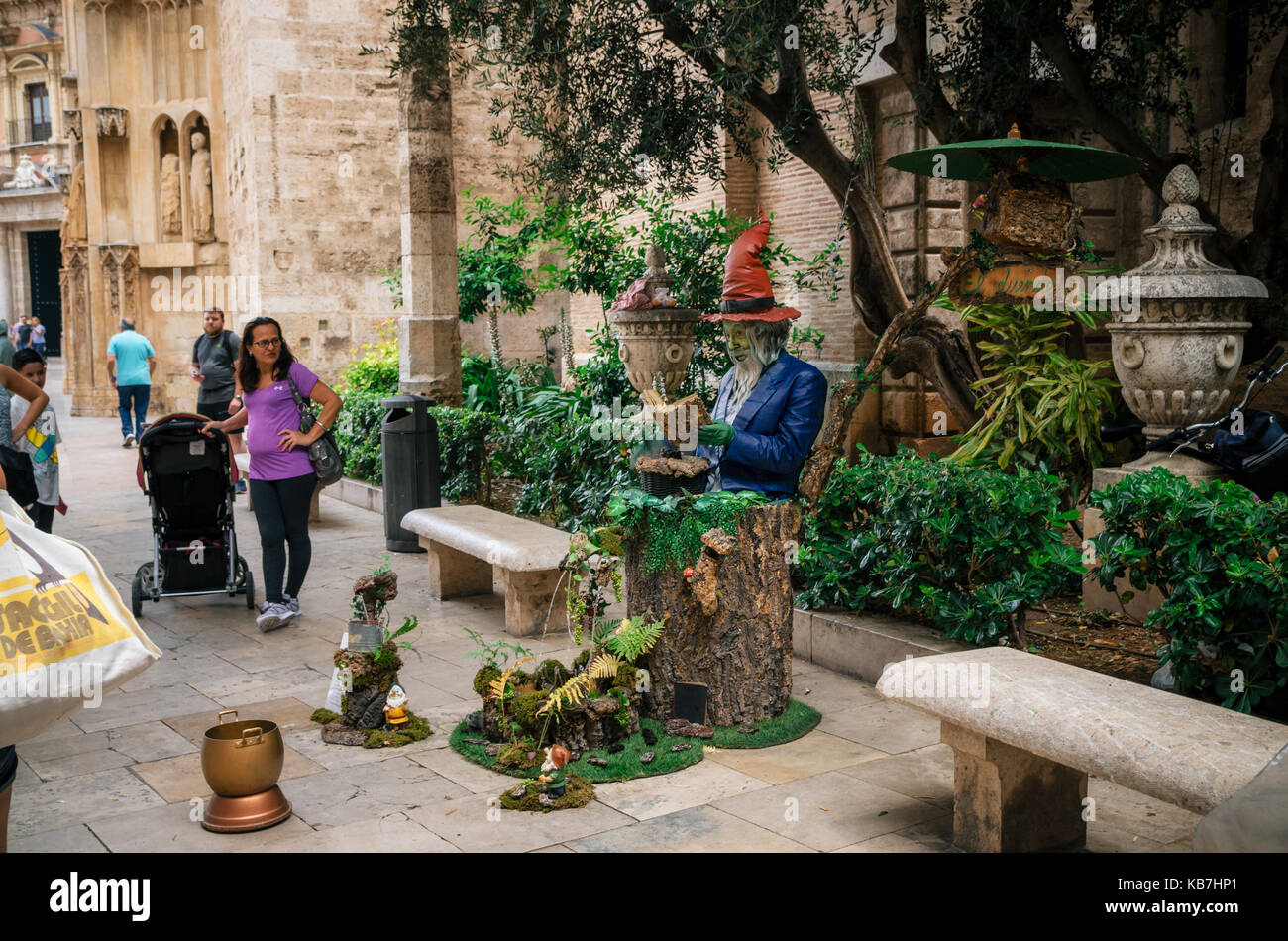 Valencia, Spain - June 3, 2017: Living statue of a man painted in vibrant colors and seated on stump with fountain - Stock Image