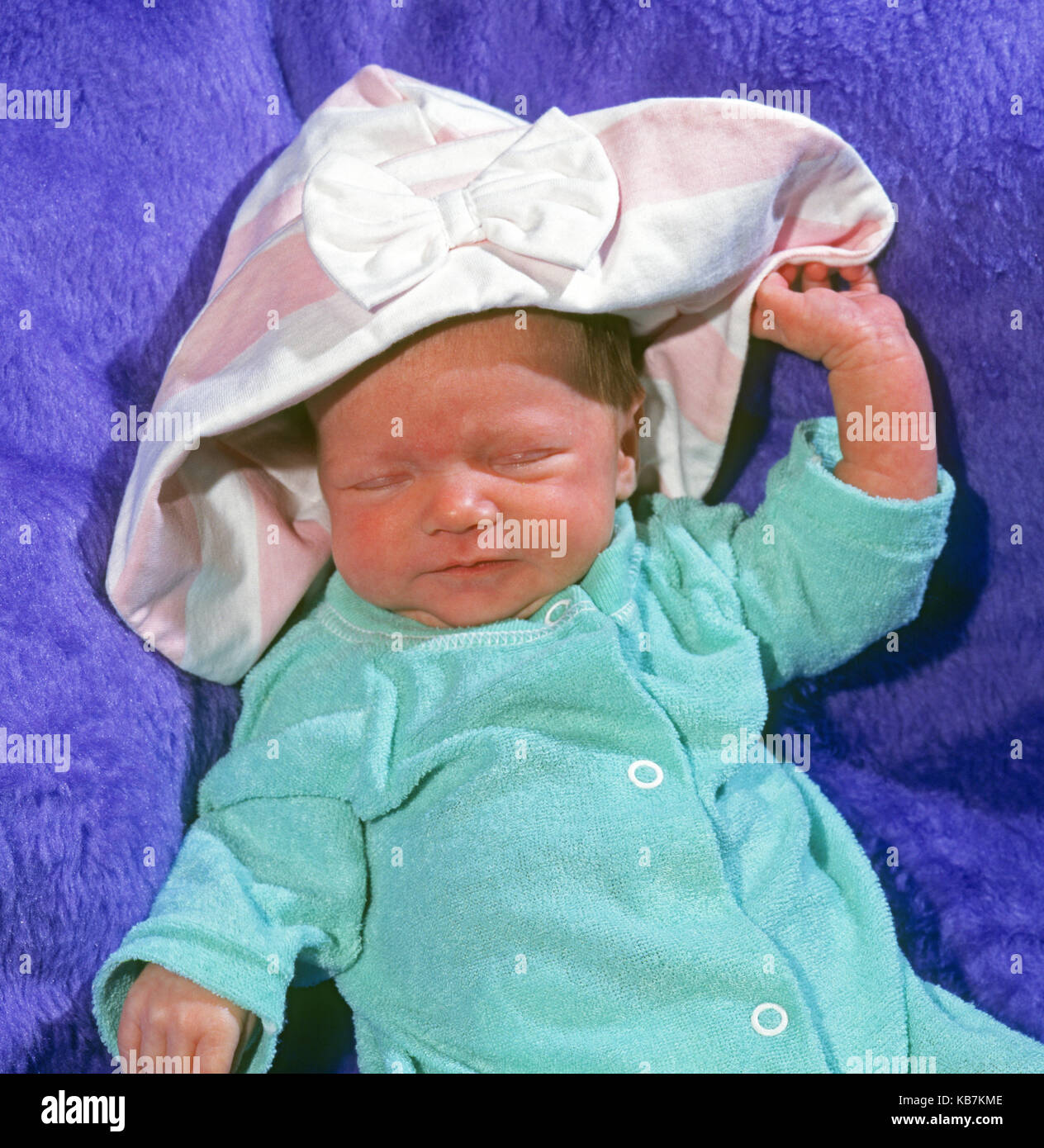 A two-week old baby wearing a onesie and a bonnet taking a nap in a blue blanket. - Stock Image