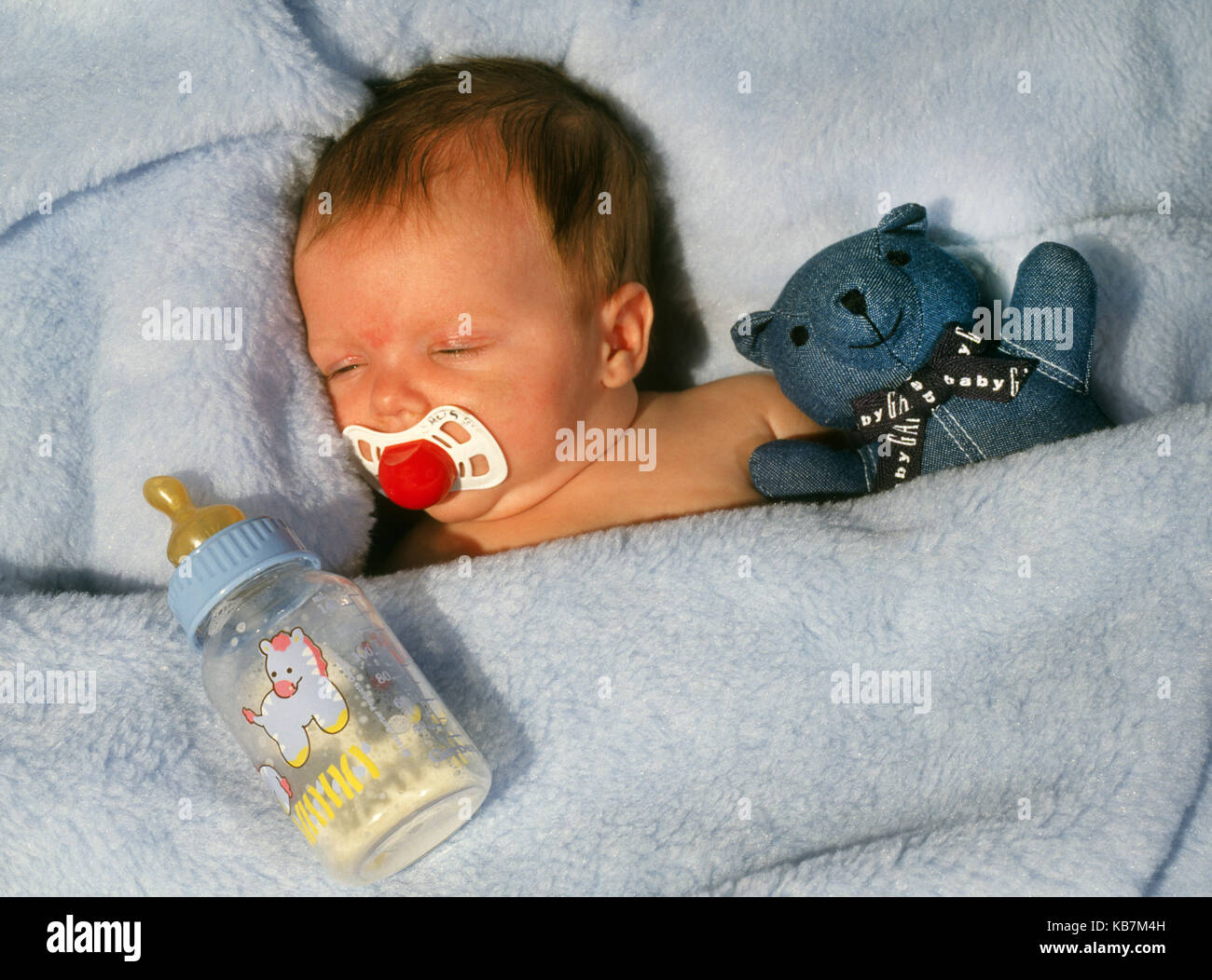 A two week old baby girl sucking on a pacifier as she sleeps Stock Photo