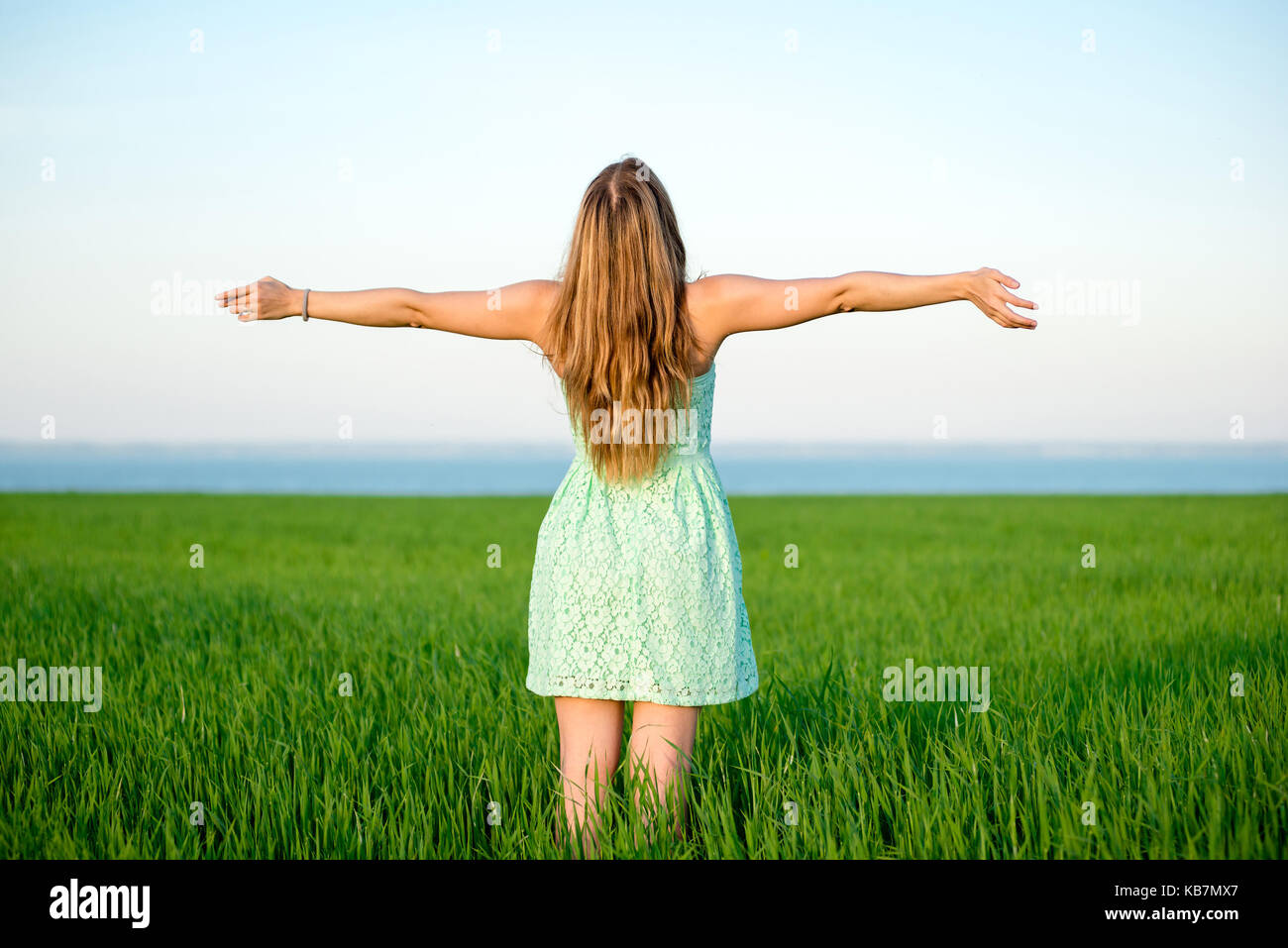 Happiness woman stay outdoor under sunlight of sunset - Stock Image