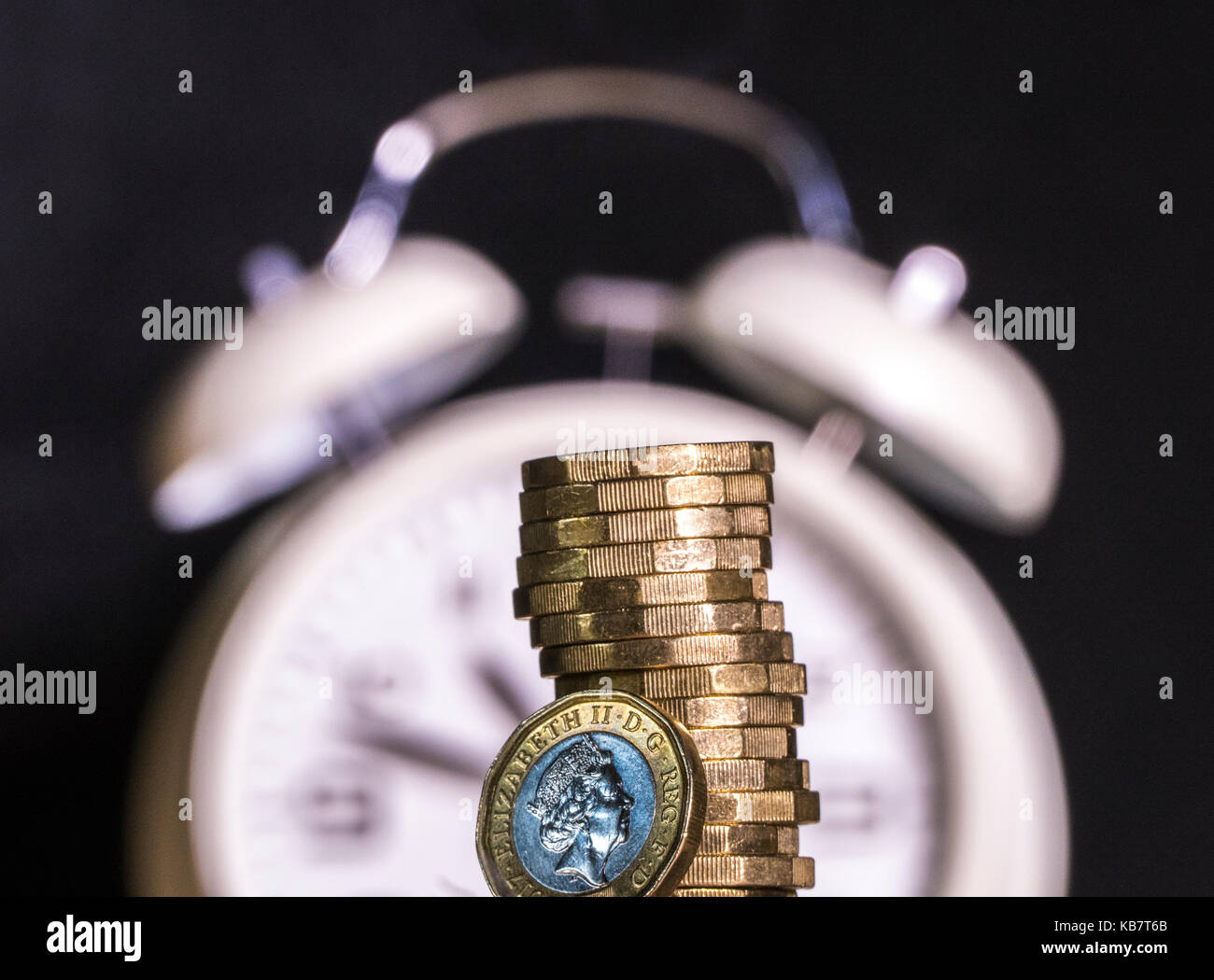 Defocused alarm clock with new pound coins. Concept of link between  timescale and British money / UK pounds sterling, - Stock Image